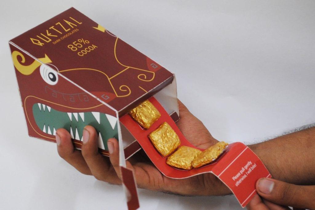 obal na čokoládu, ktorý vyzerá ako hlava draka, pričom z jeho papule možno rolovať jazyk, na ktorom sú prilepené v celofáne balené čokoládky